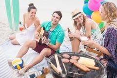 Groupe des amis avec des boissons et de la guitare se reposant à côté d'un barbecue Photo libre de droits
