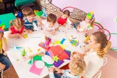 Groupe des enfants et du professeur par vue de table d'en haut Image stock