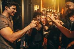 Groupe des hommes et de femmes appréciant des boissons à la boîte de nuit Photo libre de droits
