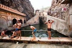 Groupe des hommes nageant dans la piscine entre les roches Photo libre de droits