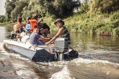 Groupe des hommes naviguant sur le canot automobile par la rivière au camp de chasse pendant la saison de chasse Photographie stock