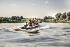 Groupe des hommes naviguant sur le canot automobile par la rivière dans le jour d'été au camping pendant la saison de chasse Photographie stock