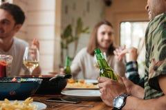 Groupe des hommes parlant et buvant de la bière à la table Photos stock