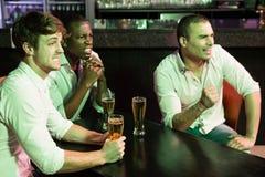 Groupe des hommes regardant la télévision dans la barre image libre de droits