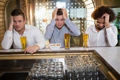 Groupe des hommes regardant la télévision dans la barre Photo stock