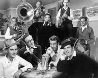 Groupe des hommes s'asseyant dans un wagon-restaurant avec des musiciens derrière eux (toutes les personnes représentées ne sont  Images stock