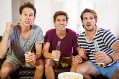 Groupe des hommes s'asseyant sur Sofa Watching Sport Together Photo libre de droits
