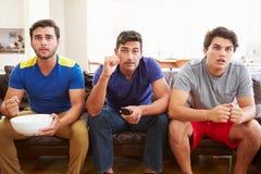 Groupe des hommes s'asseyant sur Sofa Watching Sport Together Image libre de droits