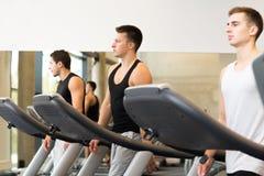 Groupe des hommes s'exerçant sur le tapis roulant dans le gymnase Photos stock
