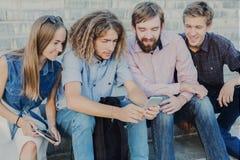 Groupe des jeunes à l'aide du smartphone dehors Images stock