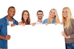 Groupe des jeunes autour du texte d'attente Images stock