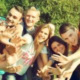 Groupe des jeunes avec des mains ensemble souriant et ayant l'amusement Images libres de droits