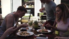 Groupe des jeunes avec des enfants prenant le déjeuner dans un café sur la rue banque de vidéos