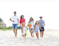 Groupe des jeunes avec des enfants sur le hêtre Photo stock