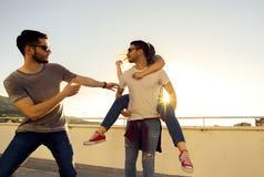 Groupe des jeunes ayant l'amusement à un dessus de toit sur le coucher du soleil photos libres de droits