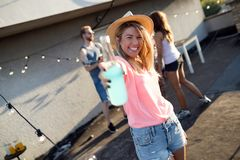 Groupe des jeunes ayant l'amusement à une partie d'été, au coucher du soleil images stock