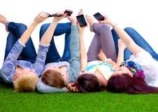 Groupe des jeunes ayant l'amusement dans l'herbe Image libre de droits
