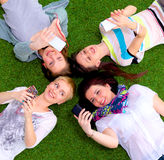 Groupe des jeunes ayant l'amusement dans l'herbe Photo stock