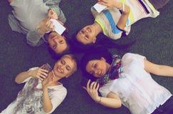Groupe des jeunes ayant l'amusement dans l'herbe Photographie stock