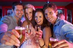 Groupe des jeunes ayant l'amusement dans le bar occupé Photographie stock