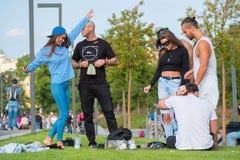Groupe des jeunes ayant l'amusement dans le parc au temps de jour Images stock