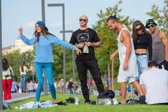 Groupe des jeunes ayant l'amusement dans le parc au temps de jour Images libres de droits