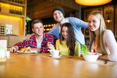 Groupe des jeunes ayant l'amusement en café Photo stock