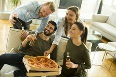 Groupe des jeunes ayant la partie de pizza Image libre de droits