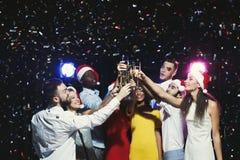 Groupe des jeunes célébrant la nouvelle année avec le champagne à la boîte de nuit Photographie stock libre de droits