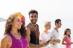 Groupe des jeunes courant sur le sourire heureux de plage, de coureurs de sport de course de mélange pulsant établissant la forme Images stock