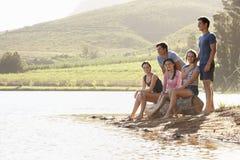 Groupe des jeunes détendant au rivage du lac Photos stock