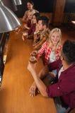Groupe des jeunes dans la barre, amis s'asseyant au contre- bar en bois, bière de boissons Photo stock