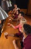 Groupe des jeunes dans la barre, amis s'asseyant au contre- bar en bois, bière de boissons Photographie stock