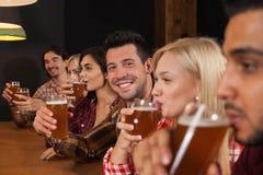 Groupe des jeunes dans la barre, amis s'asseyant au contre- bar en bois, bière de boissons Image stock