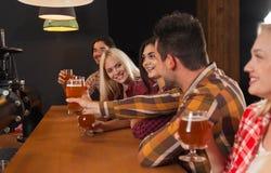 Groupe des jeunes dans la barre, amis s'asseyant au contre- bar en bois, bière de boissons Images libres de droits