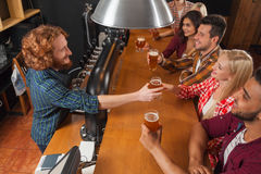 Groupe des jeunes dans la barre, bar en bois de Friends Sitting At de barman contre-, bière de boissons Photo stock