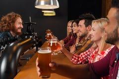Groupe des jeunes dans la barre, verres de bière de prise, amis s'asseyant au contre- bar en bois, pain grillé Images stock