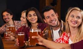 Groupe des jeunes dans la barre, verres de bière de prise parlant, amis s'asseyant au bar de causerie de Tableau en bois, sourire Photographie stock libre de droits