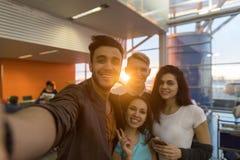 Groupe des jeunes dans les amis heureux de attente de course de mélange de sourire de départ de salon d'aéroport prenant la photo Photographie stock
