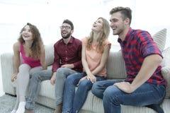 Groupe des jeunes de sourire s'asseyant sur le divan Photo libre de droits