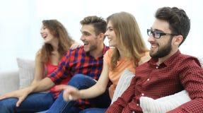 Groupe des jeunes de sourire s'asseyant sur le divan Image libre de droits