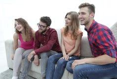 Groupe des jeunes de sourire s'asseyant sur le divan Photo stock