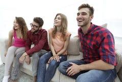 Groupe des jeunes de sourire s'asseyant sur le divan Images libres de droits