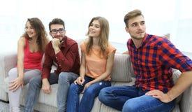 Groupe des jeunes de sourire s'asseyant sur le divan Photos stock