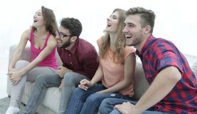 Groupe des jeunes de sourire s'asseyant sur le divan Photographie stock