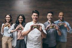 Groupe des jeunes de sourire tenant des hamburgers avec de petits drapeaux américains Image stock