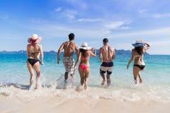 Groupe des jeunes des vacances d'été de plage, amis en bord de la mer de l'eau Images libres de droits