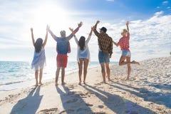 Groupe des jeunes des vacances d'été de plage, bord de la mer augmenté d'amis de mains Photos stock