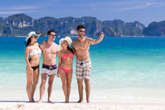 Groupe des jeunes des vacances d'été de plage, deux amis de sourire heureux de couples prenant la photo de Selfie Image stock
