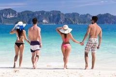 Groupe des jeunes des vacances d'été de plage, deux couples tenant le bord de la mer de marche d'amis de mains Images stock